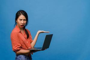 jeune femme asiatique utilisant un ordinateur portable avec une expression négative, hurlant d'excitation, pleurant émotionnellement en colère dans un tissu décontracté et se tenant isolée sur fond bleu avec un espace de copie vierge. concept d'expression faciale. photo