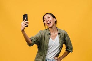 souriante adorable femme asiatique faisant une photo de selfie sur un téléphone intelligent avec une expression positive dans des vêtements décontractés et se tenant isolée sur fond jaune. heureuse adorable femme heureuse se réjouit du succès.
