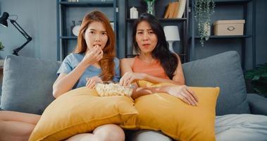 attrayant asie beau couple dame positive heureuse joyeuse avec décontracté s'amuser et profiter du moment regarder des films en ligne sur le canapé dans le salon à la maison. concept de quarantaine d'activité de mode de vie. photo