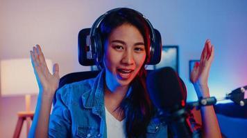 une influenceuse de musique de blogueuse asiatique heureuse regardant un enregistrement de diffusion de caméra porter un casque en ligne parler en direct dans un microphone avec le public dans le home studio du salon la nuit. concept de créateur de contenu. photo