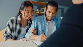 Heureux couple de jeunes clients asiatiques prêts à signer un accord de prêt bancaire pour une nouvelle maison avec un agent de courtage, un mari et une femme souriants envisagent de financer un contrat d'assurance-investissement ensemble devant le courtier. photo