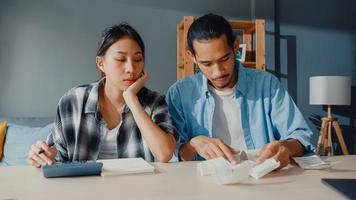 stress asie couple homme et femme utilisent la calculatrice pour calculer le budget familial, les dettes, les dépenses mensuelles pendant la crise économique financière à la maison. problème d'argent de mariage, concept de planification du budget familial. photo
