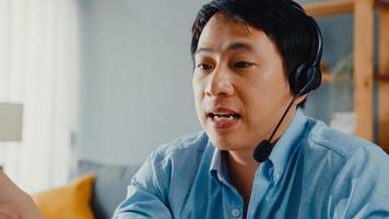 un jeune homme d'affaires asiatique porte des écouteurs à l'aide d'un ordinateur portable et parle à ses collègues du plan lors d'un appel vidéo pendant qu'il travaille à domicile dans le salon. auto-isolement, distanciation sociale, quarantaine pour la prévention du covid. photo