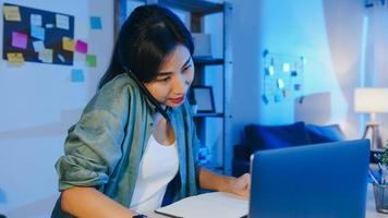 femmes asiatiques indépendantes utilisant un ordinateur portable parlant au téléphone entrepreneur occupé travaillant à distance dans le salon. travailler à partir de la surcharge de la maison la nuit, travail à distance, distanciation sociale, quarantaine pour le coronavirus. photo