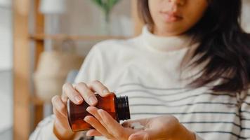 jeune femme asiatique malade tenant une pilule jette un œil à la médecine s'asseoir sur un canapé à la maison., femme prenant des médicaments après ordre du médecin, quarantaine à la maison, concept de quarantaine de distanciation sociale du coronavirus. photo