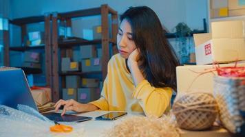 une jeune femme d'affaires asiatique regarde autour d'une pièce pleine de produits et d'une boîte à colis se sent stressée et contrariée par une mauvaise vente au bureau à domicile la nuit. propriétaire de petite entreprise, concept de livraison de marché en ligne. photo