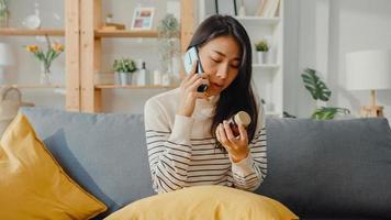 une jeune femme asiatique malade tient un médicament assis sur un canapé utilise un appel de smartphone pour consulter un médecin à la maison. la fille prend des médicaments après l'ordonnance du médecin, mise en quarantaine à la maison, concept de coronavirus de distanciation sociale. photo