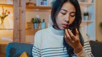 Une jeune femme asiatique malade tenant une pilule regarde la médecine s'asseoir sur un canapé à la maison la nuit. fille prenant des médicaments après l'ordonnance du médecin, mise en quarantaine à la maison, concept de soins de santé de distanciation sociale du coronavirus. photo