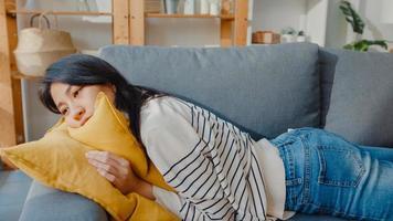jeune femme asiatique s'allonge sur un canapé confortable dans le salon pour dormir après une dure journée de travail et se sentir malade et mal, une femme fatiguée s'endort sur un canapé à la maison, fait la sieste ou la rêverie, concept de fatigue. photo