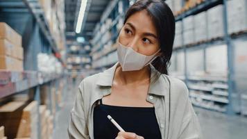 une jeune femme d'affaires asiatique porte un masque facial à la recherche de marchandises à l'aide d'une tablette numérique vérifiant les niveaux d'inventaire dans le centre commercial de détail. distribution, logistique, colis prêts à être expédiés. photo