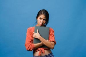 une jeune femme asiatique tient un ordinateur portable avec une expression négative, des cris excités, des cris émotionnels en colère dans un tissu décontracté et se tient isolée sur fond bleu avec un espace de copie vierge. concept d'expression faciale. photo