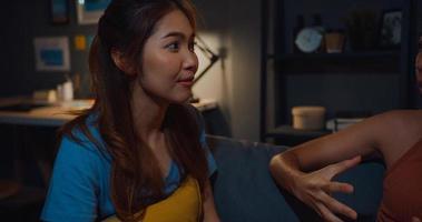 des femmes asiatiques attrayantes et heureuses avec une détente décontractée sur le canapé discutent ensemble de leur vie et de leurs potins relationnels dans le salon la nuit à la maison. Les colocataires des amies restent ensemble dans un dortoir. photo