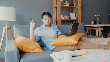 vêtements décontractés pour hommes asiatiques indépendants utilisant un ordinateur portable apprenant en ligne dans le salon de la maison. travail à domicile, travail à distance, enseignement à distance, distanciation sociale, quarantaine pour la prévention du virus corona. photo