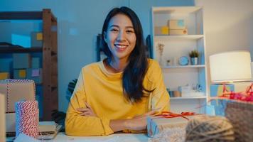 portrait d'une jeune femme d'affaires asiatique se sentant un sourire heureux, les bras croisés et regardant la caméra tout en travaillant dans un magasin au bureau à domicile la nuit. propriétaire de petite entreprise, concept de livraison de marché en ligne. photo
