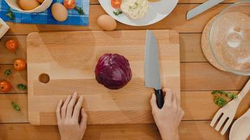 main de jeune femme asiatique chef tenir le couteau coupant le chou rouge sur une planche de bois sur la table de la cuisine dans la maison. cuisiner une salade de légumes, une alimentation saine et un concept naturel traditionnel. vue de dessus. photo