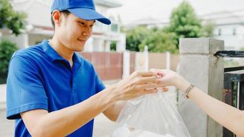 jeune homme de messagerie de livraison postale d'asie en chemise bleue manipulant des boîtes de nourriture pour l'envoi au client à la maison et une femme asiatique reçoit un colis livré à l'extérieur. concept de livraison de nourriture d'achats de colis. photo