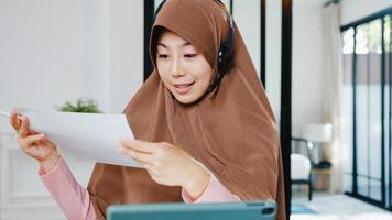 une dame musulmane d'asie porte un casque à l'aide d'une tablette numérique parle à des collègues du rapport de vente lors d'une conférence vidéo tout en travaillant à domicile dans la cuisine. distanciation sociale, quarantaine pour le virus corona. photo