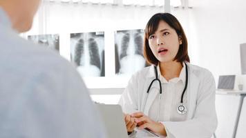 une jeune femme médecin asiatique en uniforme médical blanc utilisant un ordinateur portable donne d'excellentes nouvelles pour discuter des résultats ou des symptômes avec un patient masculin assis au bureau dans une clinique de santé ou un bureau d'hôpital. photo