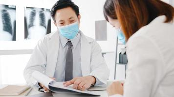 un médecin asiatique sérieux porte un masque de protection à l'aide d'un presse-papiers donne d'excellentes nouvelles discutent des résultats ou des symptômes avec une patiente au bureau de l'hôpital. mode de vie nouveau normal après le virus corona. photo