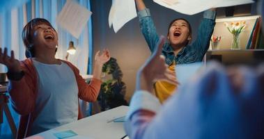 groupe multiracial jeunes asiatiques créatifs en vêtements décontractés intelligents discutant d'un geste d'affaires à la main, rire et sourire ensemble lors d'une réunion de remue-méninges au bureau de nuit. concept de travail d'équipe de collègue. photo