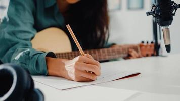 Une femme asiatique heureuse, une auteure-compositrice, joue de la guitare acoustique, écoute une chanson à partir d'un smartphone, pense et écris des paroles de chansons en papier assis dans le salon du home studio. production musicale à la maison concept. photo