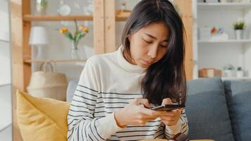 jeune femme asiatique malade tenir un médicament assis sur un canapé prendre une photo envoyée au médecin à la maison. la fille prend des médicaments après l'ordonnance du médecin, mise en quarantaine à la maison, concept de quarantaine de distanciation sociale du coronavirus.