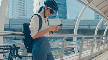 une femme d'affaires asiatique heureuse avec un sac à dos utilise un téléphone intelligent dans un stand de ville dans la rue avec un vélo pour aller travailler au bureau. fille de sport utilise son téléphone pour travailler. se rendre au travail, navetteur d'affaires en ville. photo