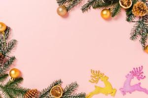 mise à plat créative minimale de la composition traditionnelle de noël et de la saison des vacances du nouvel an. vue de dessus des décorations de noël d'hiver sur fond rose avec un espace vide pour le texte. copier la photographie de l'espace. photo