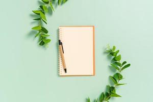 photo créative à plat du bureau de l'espace de travail. bureau vue de dessus avec des cahiers vierges de maquette ouverte et un crayon et une plante sur fond de couleur vert pastel. vue de dessus avec maquette de photographie de l'espace de copie.