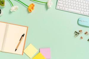 photo créative à plat du bureau de l'espace de travail. bureau vue de dessus avec clavier, souris et bloc-notes noir maquette ouverte sur fond de couleur vert pastel. vue de dessus maquette avec copie espace photographie.