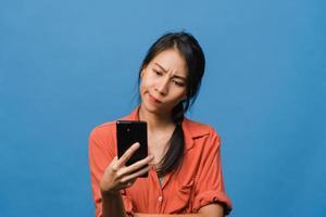 jeune femme asiatique utilisant un téléphone avec une expression positive, sourit largement, vêtue de vêtements décontractés, se sentant heureuse et isolée sur fond bleu. heureuse adorable femme heureuse se réjouit du succès. photo