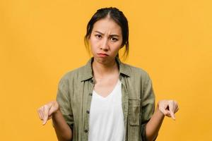 une jeune femme asiatique montre quelque chose d'étonnant dans un espace vide avec une expression négative, des cris excités, des pleurs émotionnels en colère en regardant la caméra isolée sur fond jaune. concept d'expression faciale. photo