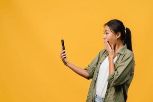 jeune femme asiatique utilisant un téléphone avec une expression positive, sourit largement, vêtue de vêtements décontractés, se sentant heureuse et isolée sur fond jaune. heureuse adorable femme heureuse se réjouit du succès. photo