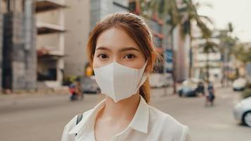 Une jeune femme d'affaires asiatique réussie dans des vêtements de bureau de mode porte un masque médical souriant et regardant la caméra tout en étant heureuse seule à l'extérieur dans une ville urbaine moderne. concept d'entreprise en déplacement. photo