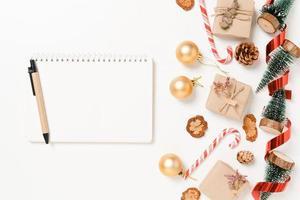 mise à plat créative minimale de la composition traditionnelle de noël d'hiver et de la saison des vacances du nouvel an. vue de dessus ouvrir le cahier noir de maquette pour le texte sur fond blanc. maquetter et copier la photographie spatiale. photo