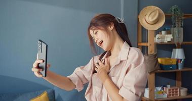 une jeune fille asiatique heureuse et insouciante utilise un appel vidéo sur smartphone et profite de la conversation avec un ami d'université dans le salon à la maison. concept de pandémie de coronavirus à distance sociale. concept de liberté et de mode de vie actif. photo
