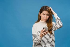 pensant rêver d'une jeune femme asiatique utilisant un téléphone avec une expression positive, vêtue de vêtements décontractés, se sentant heureuse et isolée sur fond bleu. heureuse adorable femme heureuse se réjouit du succès. photo