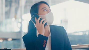Une fille d'affaires asiatique intelligente porte un costume assis avec une valise sur un banc, appelez un téléphone intelligent avec un partenaire, attendez le vol à l'aéroport. navetteur de voyage d'affaires dans la pandémie de covid, concept de voyage d'affaires. photo