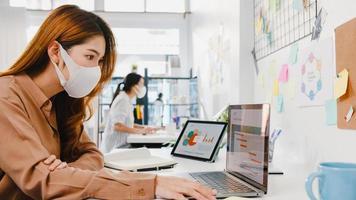 femme d'affaires asiatique entrepreneur portant un masque médical pour la distanciation sociale dans une nouvelle situation normale pour la prévention des virus tout en utilisant un ordinateur portable au travail au bureau. mode de vie après le virus corona. photo
