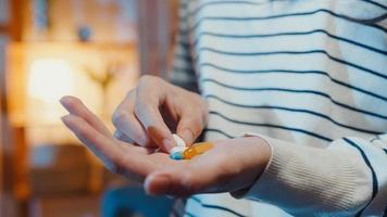 Une jeune femme asiatique malade tenant une pilule prend des médicaments s'assoit sur un canapé dans le salon la nuit à la maison. fille prenant des médicaments après l'ordonnance du médecin, mise en quarantaine à la maison, concept de soins de santé de distanciation sociale du coronavirus. photo