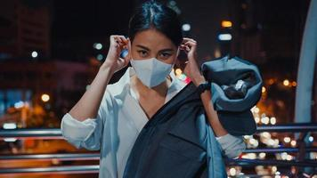 Une jeune femme d'affaires asiatique réussie dans des vêtements de bureau de mode porte un masque médical souriant et regardant la caméra tout en étant heureuse seule à l'extérieur dans la nuit de la ville moderne urbaine. concept d'entreprise en marche. photo
