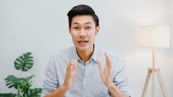 homme d'affaires asiatique distanciation sociale dans une nouvelle situation normale pour la prévention des virus en regardant la présentation de la caméra à un collègue au sujet du plan en appel vidéo pendant le travail au bureau. mode de vie après le virus corona. photo