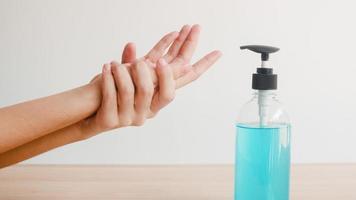 femme asiatique utilisant un désinfectant pour les mains au gel d'alcool se laver les mains pour protéger le coronavirus. une femme pousse une bouteille d'alcool pour nettoyer la main pour l'hygiène lorsque la distanciation sociale reste à la maison et le temps d'auto-quarantaine. photo
