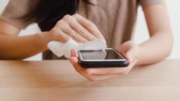 femme asiatique utilisant un spray d'alcool sur un téléphone portable propre avant de l'utiliser pour protéger le coronavirus. surface propre des femmes pour l'hygiène lorsque la distanciation sociale reste à la maison et le temps d'auto-quarantaine. photo