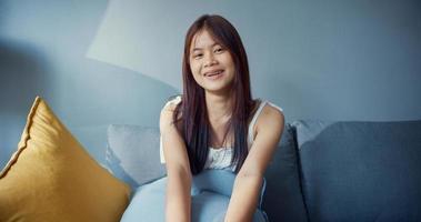 Jeune fille heureuse d'adolescent d'Asie avec un temps de détente joyeux souriant regardant la caméra dans le salon de la maison. isoler le mode de vie de l'activité, concept de pandémie de coronavirus à distance sociale. photo