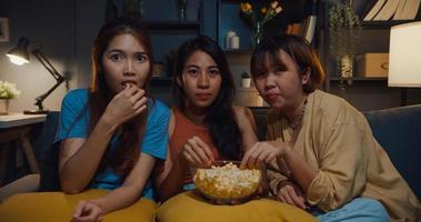 groupe de jolies filles asiatiques paniquées par la peur et le moment terrifié mangent du pop-corn regarder un film d'horreur en ligne sur un canapé dans le salon à la maison la nuit. concept de quarantaine d'activité de mode de vie le week-end. photo