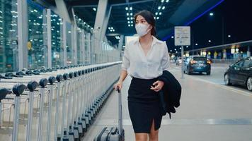 une fille d'affaires asiatique arrive à destination, portez un masque facial avec un bagage à pied à l'extérieur du terminal de voiture d'attente à l'aéroport national. pandémie de covid de banlieue d'affaires, concept de distanciation sociale de voyage d'affaires. photo