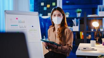 Une femme d'affaires asiatique porte un masque facial pour la distanciation sociale dans une nouvelle norme pour la présentation de la prévention des virus à un collègue sur le plan lors d'un appel vidéo pendant qu'elle travaille la nuit au bureau. mode de vie après le coronavirus. photo