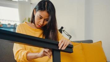 Heureuse jeune femme asiatique déballant la boîte et lisant les instructions pour assembler de nouveaux meubles décorer une table de construction de maison avec une boîte en carton dans le salon à la maison. photo