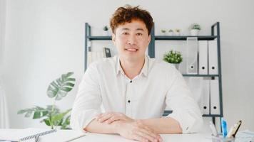 un jeune homme d'affaires asiatique utilisant un ordinateur portable parle à ses collègues du plan lors d'une réunion par appel vidéo tout en travaillant à domicile dans le salon. auto-isolement, distanciation sociale, quarantaine pour le virus corona. photo